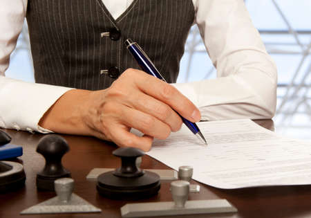 notary: Woman notary, lawyer signs the documents in office