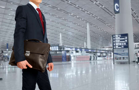 Zakenreis. Zakenman met een koffer in de luchthaven Stockfoto