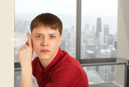 snooping: Cuckold concept.  Man spying by listening through wall with glass Stock Photo