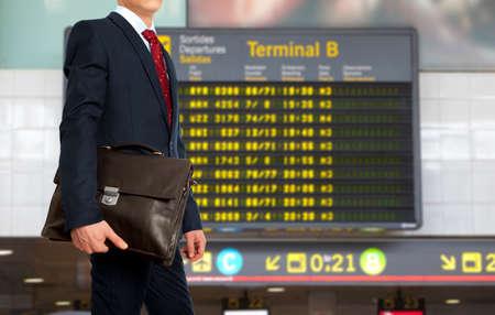 Geschäftsreise. Geschäftsmann mit einem Aktenkoffer auf dem Hintergrund der Abflugtafel am Flughafen