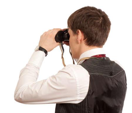 supervisión: El hombre de negocios mira a través de los prismáticos sobre un fondo blanco Foto de archivo