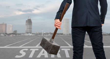 destroying the competition: Startup concept. Determined businessman with hammer in hands