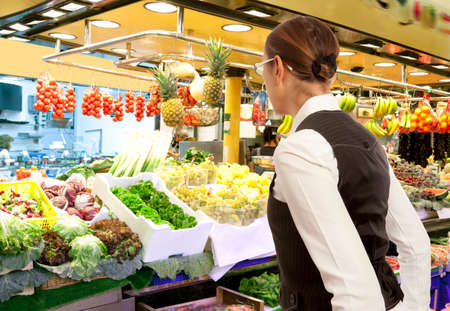 produce departments: Woman buys fresh fruits and vegetables in market. Woman looking to raw fruits and vegetables in supermarket