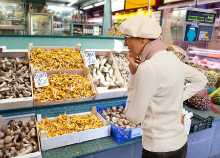 produce departments: Woman buys raw mushroom in market. Woman looking to fresh mushroom in supermarket