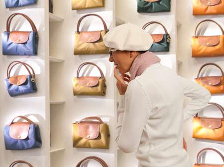 ladys: Shopping woman chooses ladys handbag in store. Woman looking to ladys handbag or shop window.