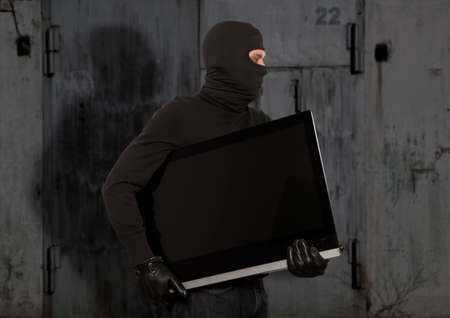 stealing: Thief with balaclava stealing computer monitor or television
