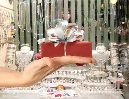 Mano femenina que sostiene un regalo en el fondo de la ventana de la joyería tienda Foto de archivo