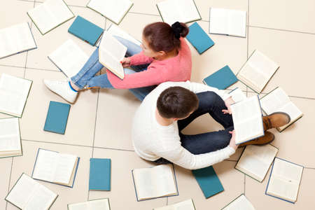 unreadable: Young woman and man reading a book, top view. Blurred text is unreadable