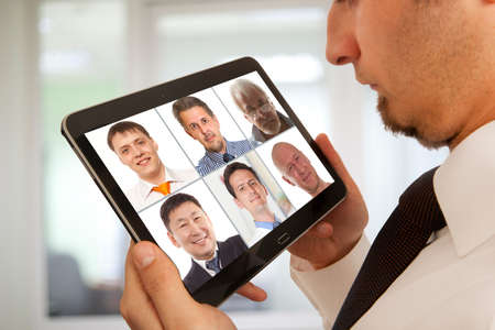 Businessman attending video conference with colleague on digital tablet photo