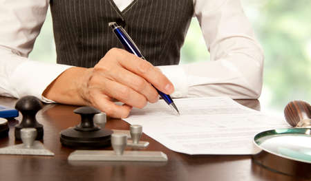 abogado: Mujer notario, abogado firma los documentos en la oficina
