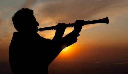 trumpeter: Trumpeter. Man playing on oboe against the background of sunset