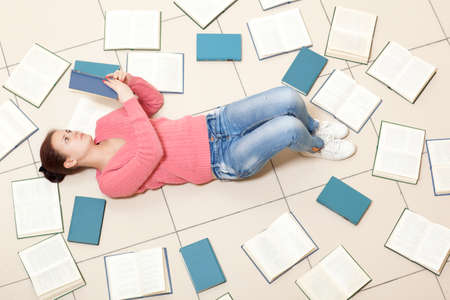 unreadable: Girl reading a book, top view. Blurred text is unreadable Stock Photo
