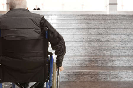 unreachable: Wheelchair user in front of staircase barrier Stock Photo