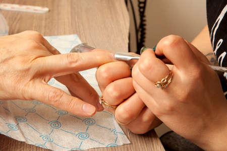 nailcare: Woman getting nail manicure. Woman in a nail salon receiving a manicure by a beautician