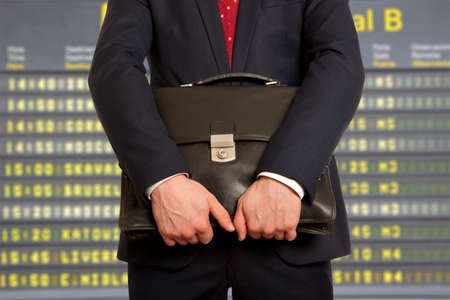 departure board: business trip. Businessman with a briefcase on a background of departure board at airport