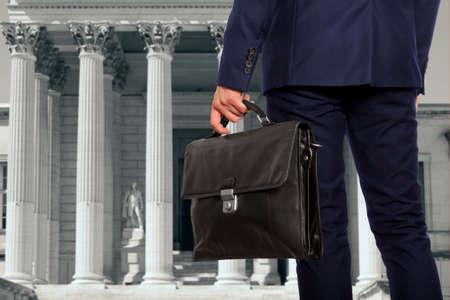 L'avocat avec une mallette est contre le palais de justice Banque d'images