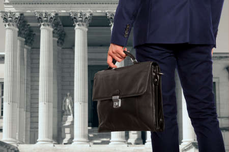 The lawyer with a briefcase is on against the courthouse Фото со стока