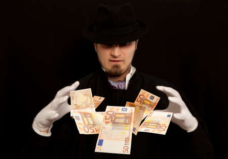 rascal: Magician show with euro banknote. Isolated on black background Stock Photo
