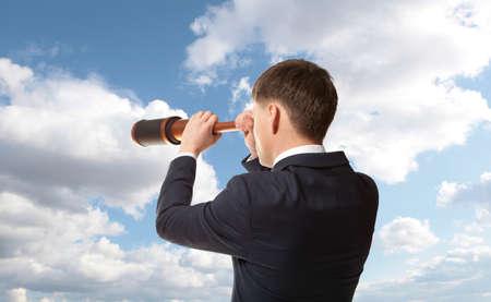Business concept. Businessman looks through a telescope