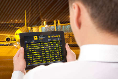 flying man: Businessman with tablet in airport with flight schedule and departure and gate information Stock Photo