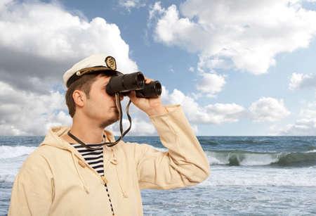 Captain looks through a binoculars. Marine concept Imagens