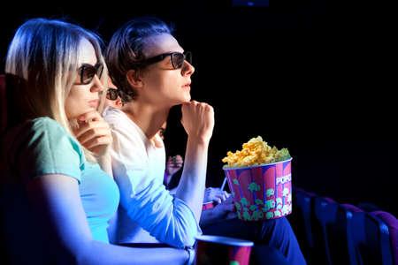jovenes felices: Pareja joven sentado en el cine, viendo una película. serie de fotos cine