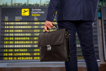 Voyage d'affaire. Homme d'affaires avec une serviette sur un fond de carte de départ à l'aéroport