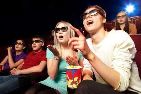 people watching: Young people sitting at the cinema, watching a film. Cinema photo series
