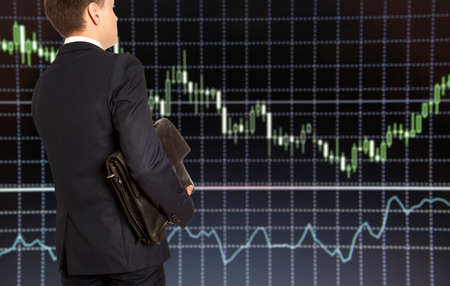 capitalist: Exchange broker. Businessman with briefcase against the background of the exchange panel Stock Photo