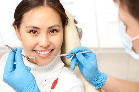 Smiling patient looking at camera while dentist examining it. Dental photo series