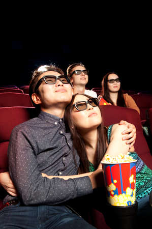 people watching: Young couple sitting at the cinema, watching a film. Cinema photo series