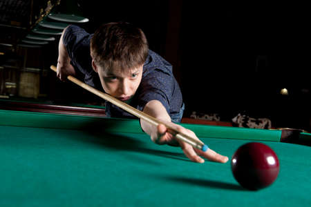 snooker room: Young man playing billiards in the dark billiard club Stock Photo
