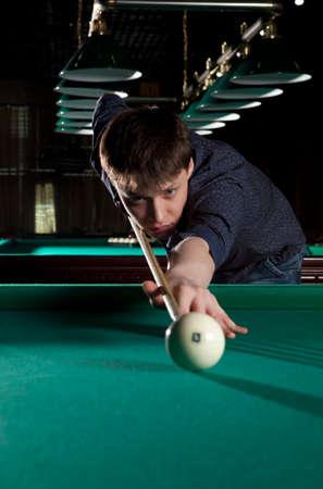 billiards hall: Young man playing billiards in the dark billiard club Stock Photo