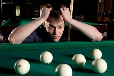 pool halls: Young man playing billiards in the dark billiard club Stock Photo