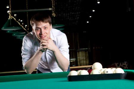 billiards room: Young man playing billiards in the dark billiard club Stock Photo