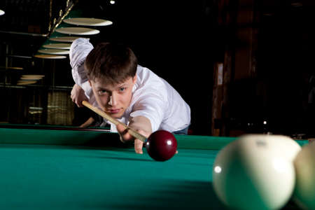 snooker halls: Young man playing billiards in the dark billiard club Stock Photo