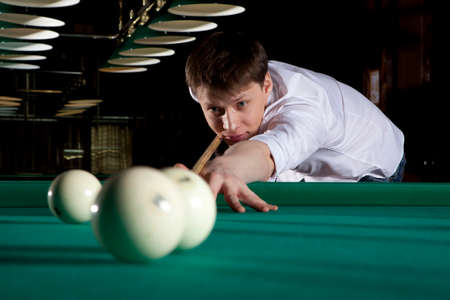 snooker hall: Young man playing billiards in the dark billiard club Stock Photo