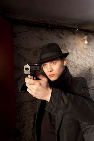 holding gun: Man holding gun against an wall background
