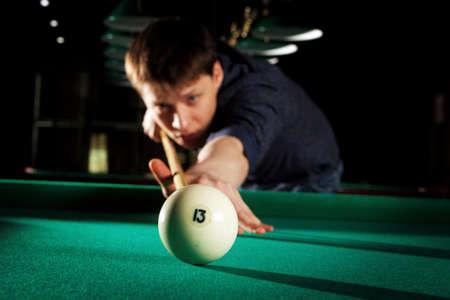 snooker halls: Number thirteen. Young man playing billiards in the dark billiard club Stock Photo