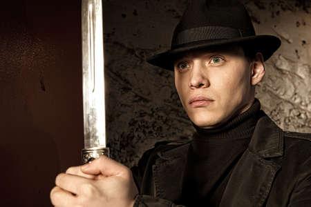 dagger: A dangerous man holding dagger on dark background