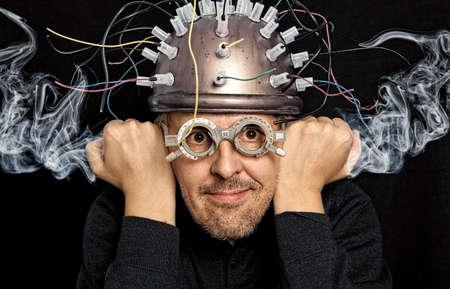 loco: inventor loco con el casco de la investigación del cerebro