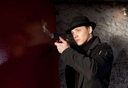 man holding gun: Man holding gun against an wall background