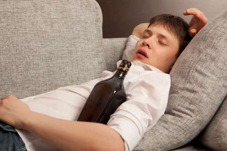 drinking problem: A young man with a drinking problem is relaxing on a sofa Stock Photo