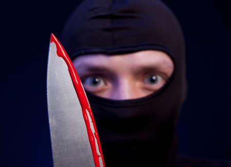 kidnapper: Man criminal in black mask with knife over dark blue background