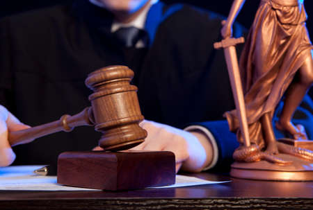 Judge. Male judge in a courtroom striking the gavel Stock Photo