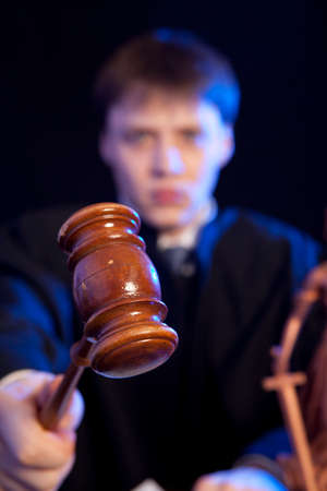 innocent: Judge. Male judge in a courtroom striking the gavel