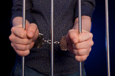 handcuffs: Hands of the prisoner on a steel lattice. Arrested man in handcuffs