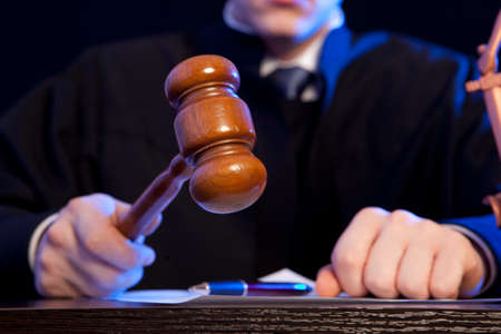 judge hammer: Judge. Male judge in a courtroom striking the gavel