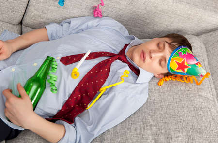 drinking problem: A young businessman with a drinking problem is relaxing on a sofa