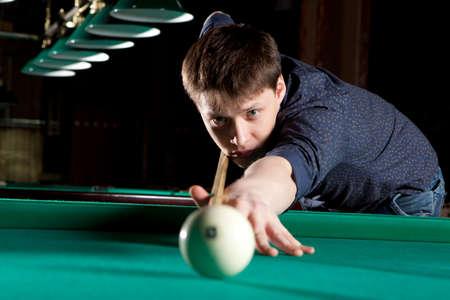 billiards rooms: Young man playing billiards in the dark billiard club Stock Photo
